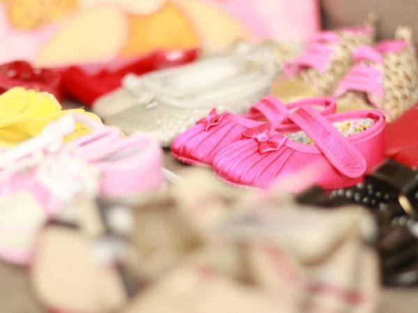 Imagem mostra diversas sapatilhas infantis dentre outros modelos de sapato para crianças.