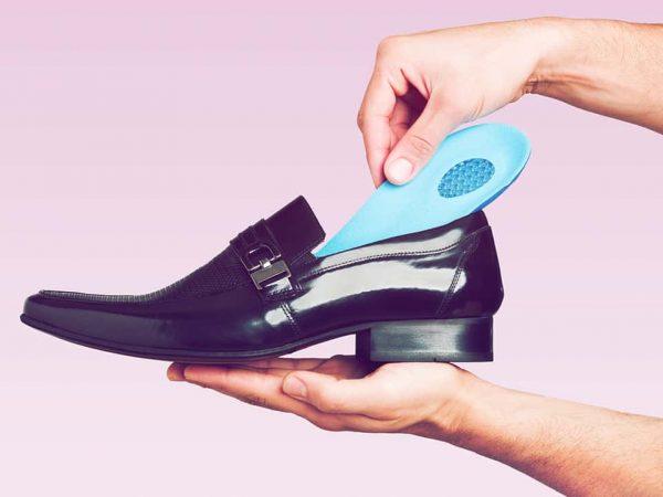 Na foto um homem colocando uma palmilha de gel em um sapato social.