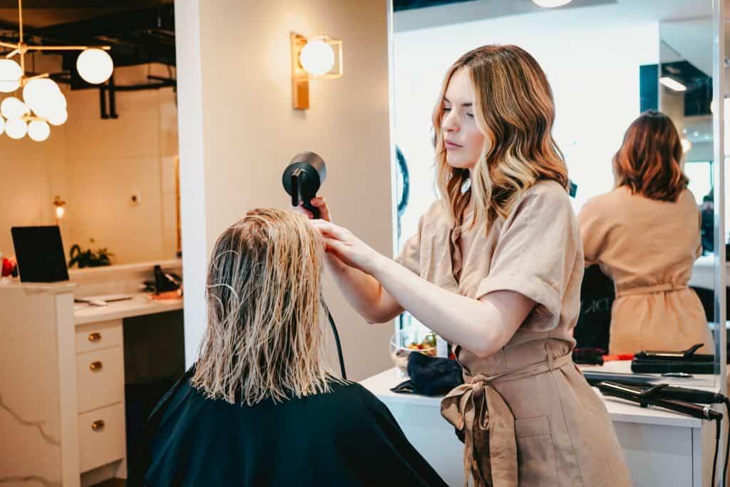 Imagem de uma cabeleireira secando o cabelo da cliente.
