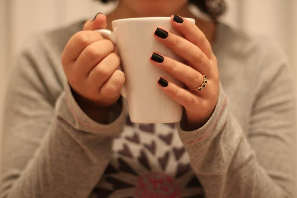 Na foto uma mulher segurando uma xícara.