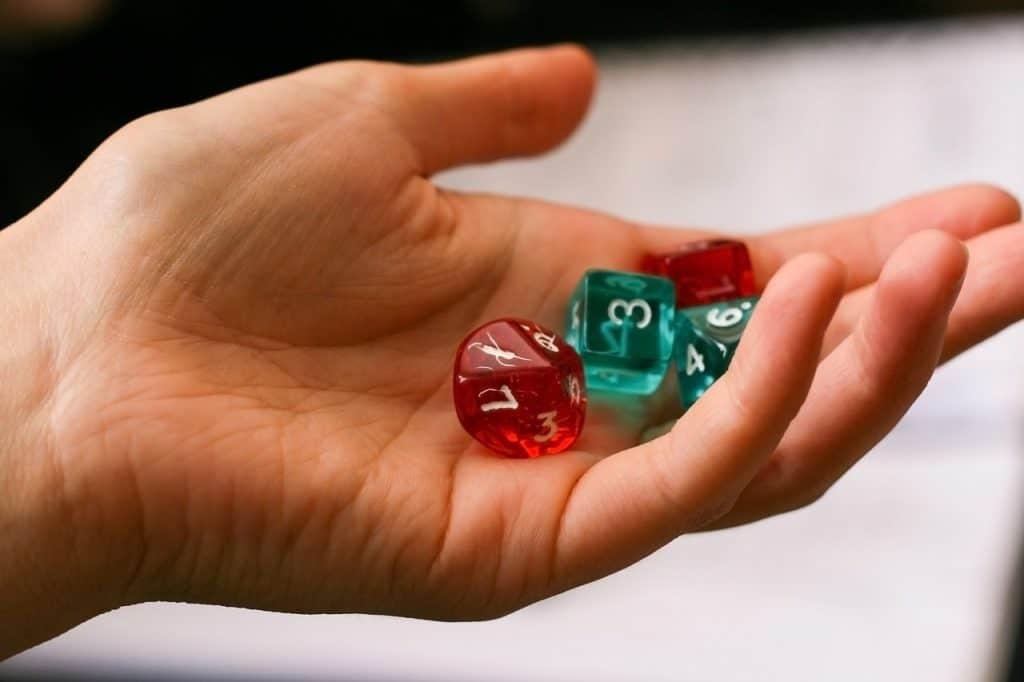 Uma mão de uma pessoa segura 4 dados de RPG.
