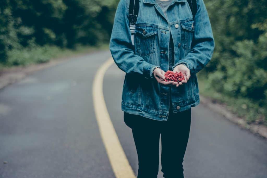 Imagem mostra uma mulher parada no meio da via de uma estrada, segurando um punhado de frutinhas nas palmas das mãos.