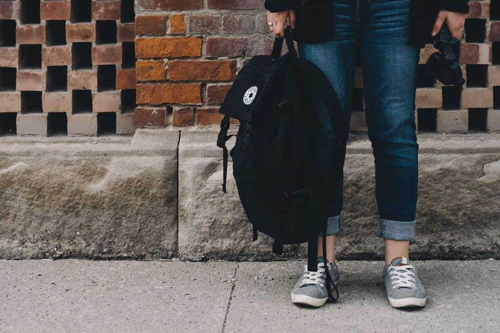 Imagem de uma pessoa segurando uma mochila.