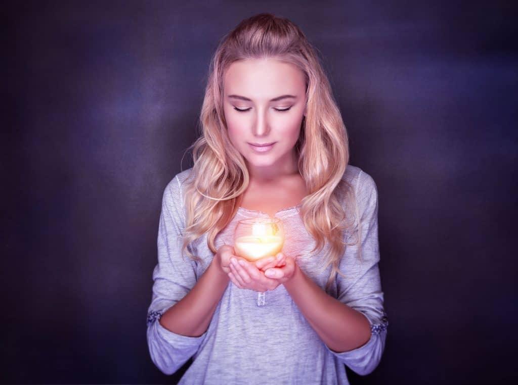 Imagem de mulher segurando uma luminária com vela dentro.