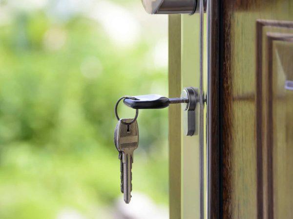 Imagem da porta de uma casa com uma chave na fechadura.