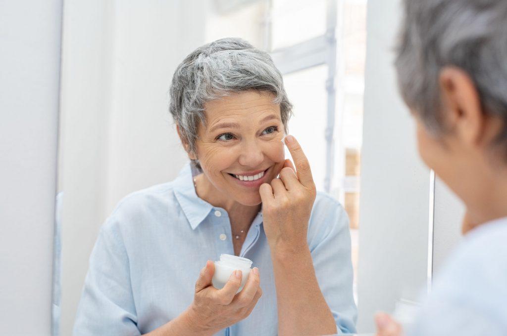 Na foto uma mulher aplicando creme no rosto em frente a um espelho.