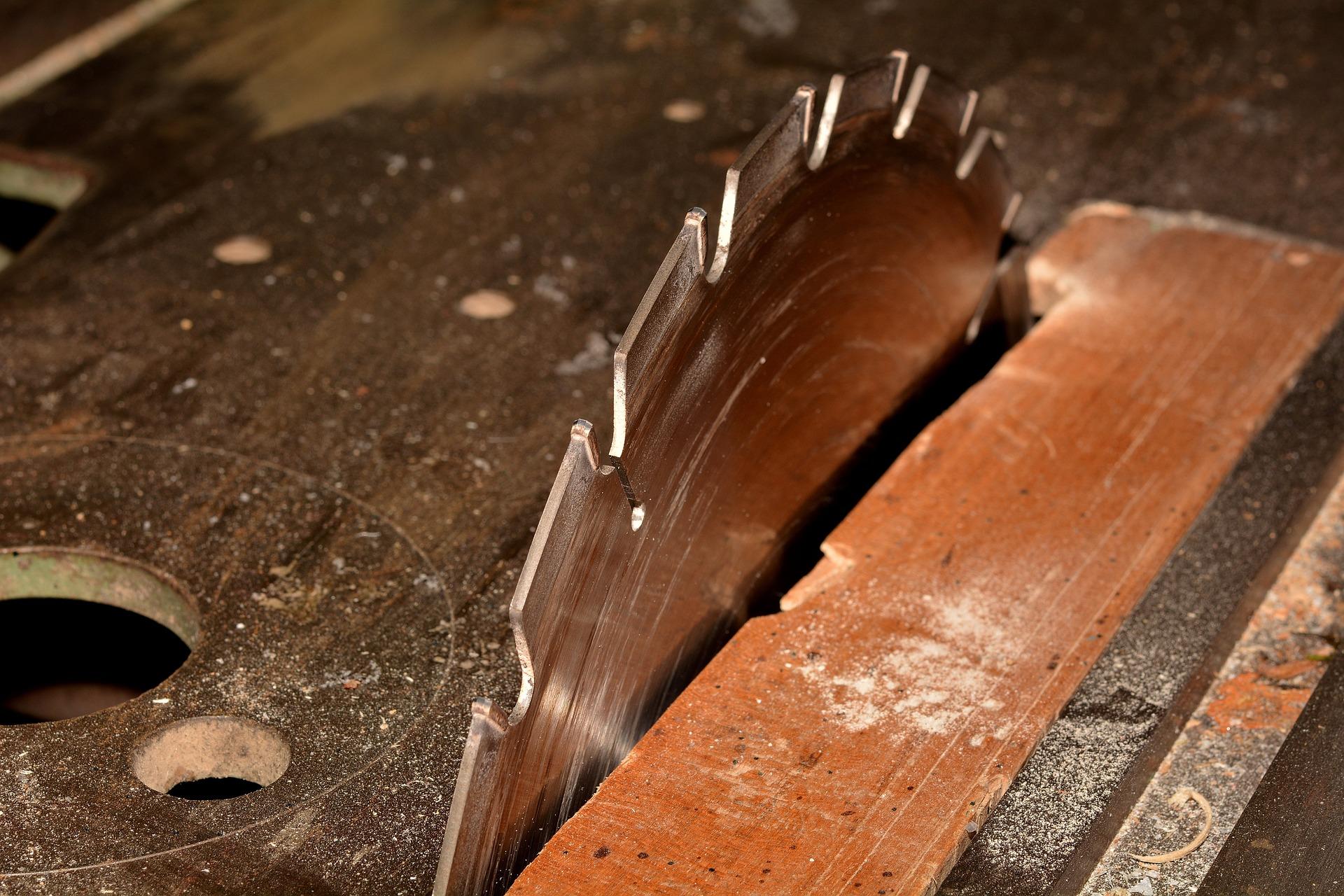foto do disco de serra de uma serra circular de bancada em funcionamento, cortando parte de uma tábua posicionada.