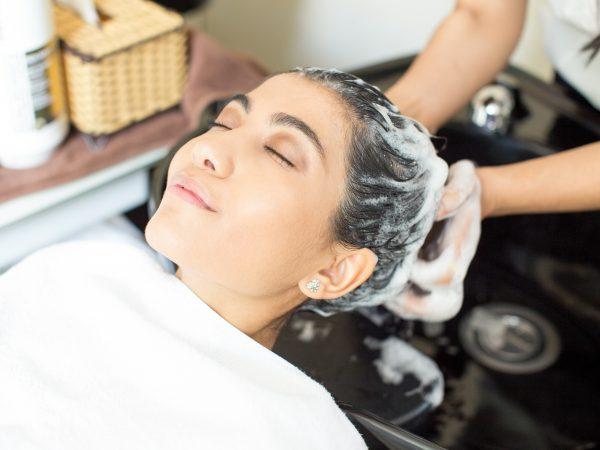 Imagem de mulher com a cabeça em uma pia e as mãos de outra pessoas na cabeça dela ensaboando seus cabelos.