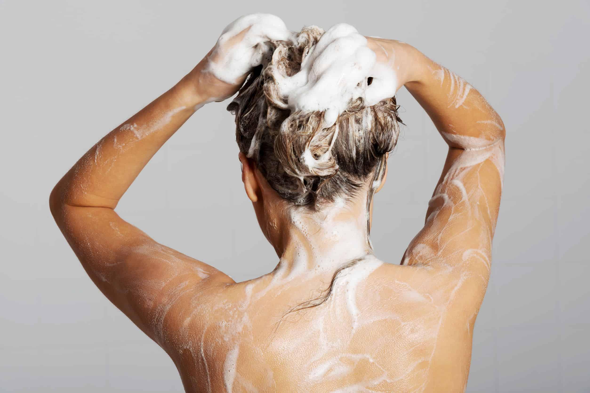 Foto de uma mulher de costas, tomando banho e com espuma nos cabelos.