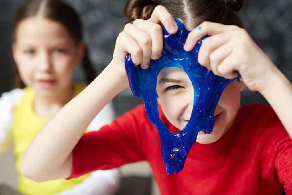 Menina sorri enquanto brinca com slime azul em frente ao rosto.