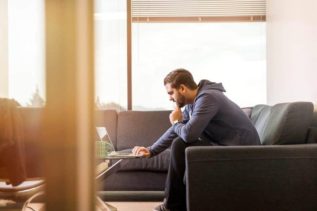 Na foto um homem de moletom sentado em um sofá cinza de canto usando um notebook.