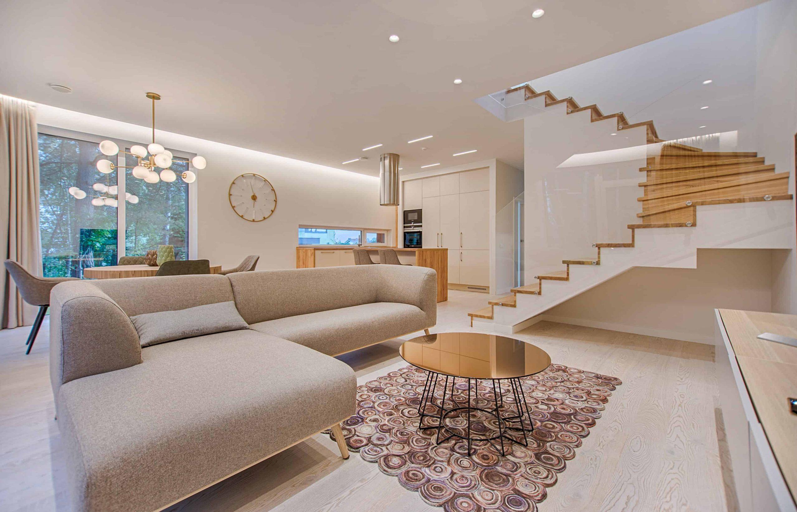 Na foto uma sala de estar com um sofá cinza claro, mesa de centro dourada e escada em madeira.