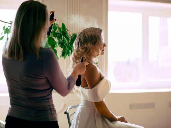 Na foto um mulher borrifando spray fixador de cabelo em outra.
