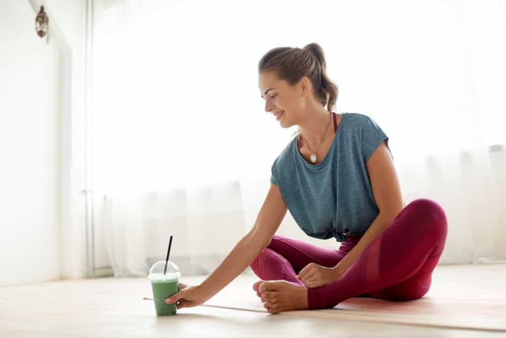 Imagem de uma mulher tomando um smoothie de espirulina.