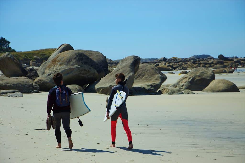 Imagem mostra dois rapazes caminhando pela praia, cada um carregando uma prancha de bodyboard debaixo do braço.