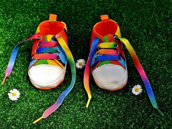 Tênis multicolorido com cadarços com as cores do arco-íris em um gramado com flores.