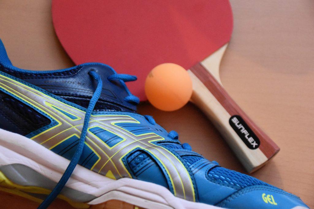 Tênis Asics ao lado de raquete e bola de tênis de mesa.