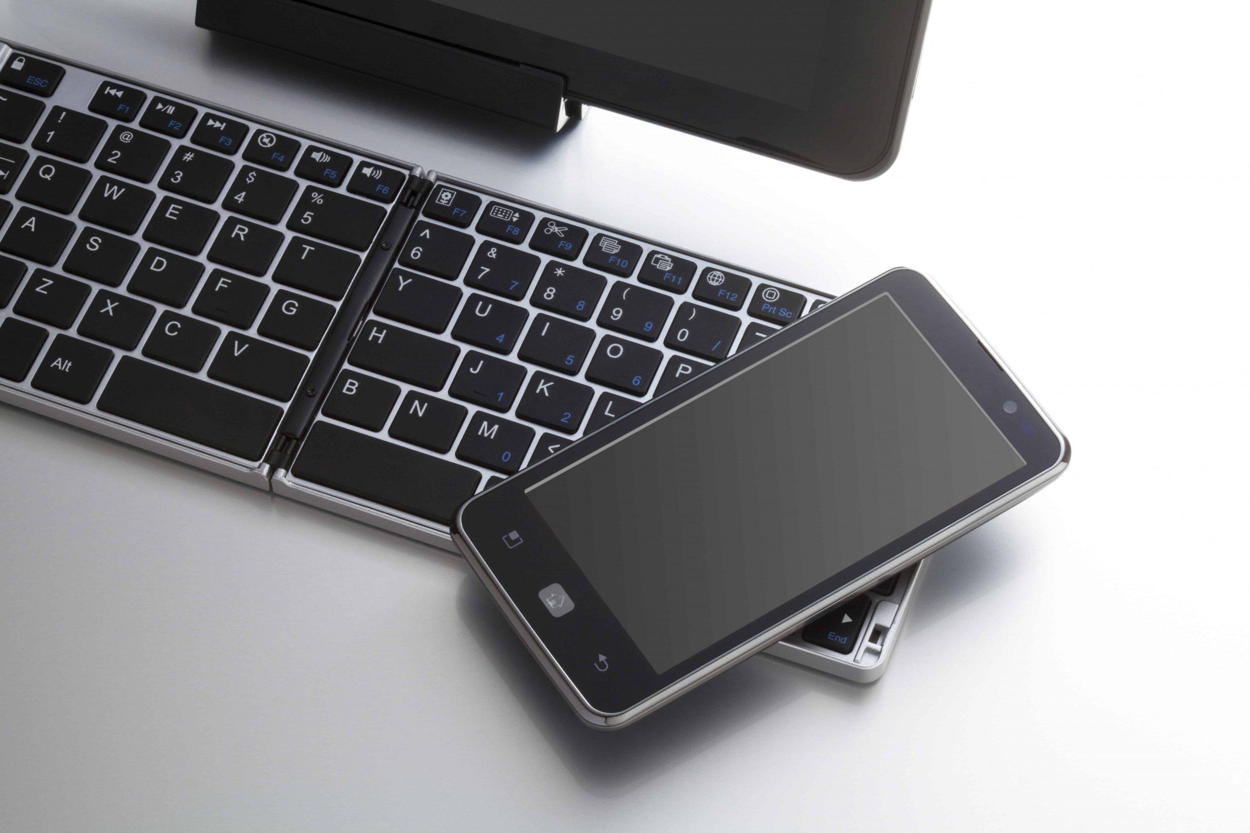 Imagem de um teclado dobrável com um celular em cima.