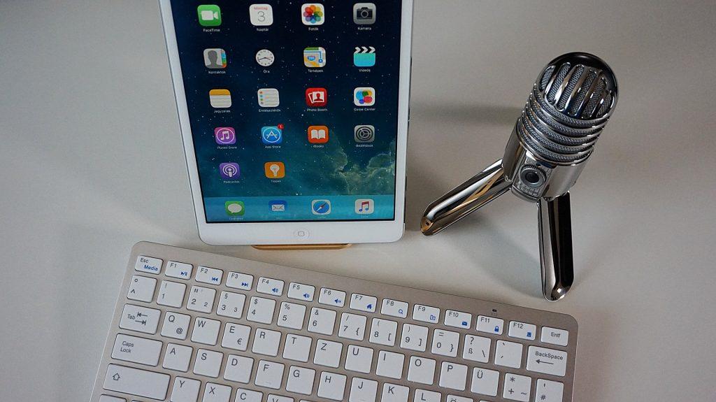 Imagem com um teclado, um tablet e uma webcam no formato de microfone.