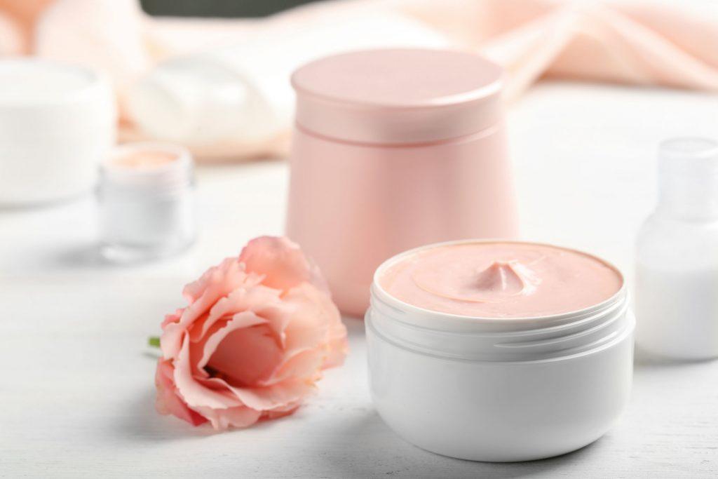 Foto mostra um creme hidratante rosa.