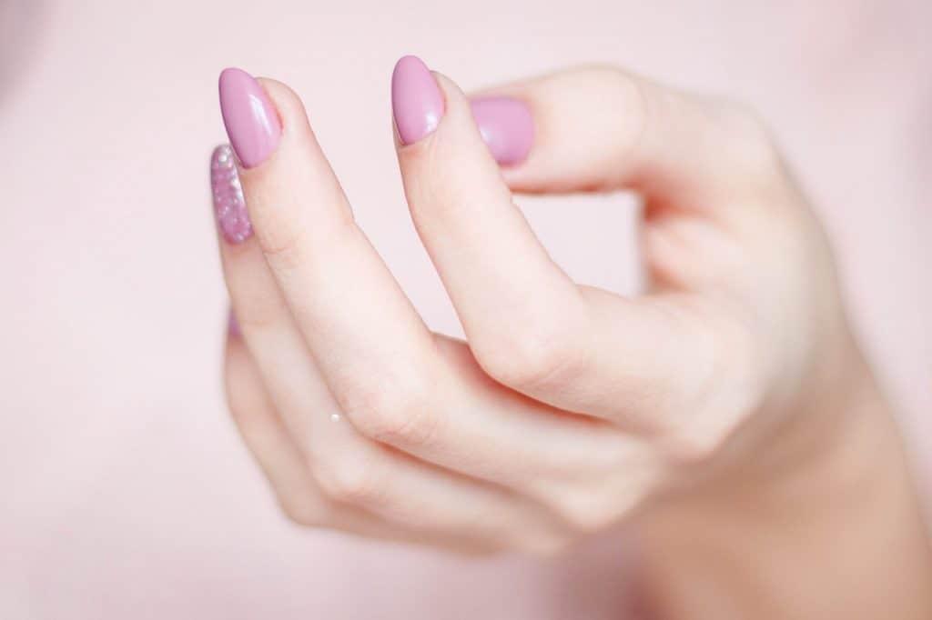 Na foto as mãos de uma mulher com unhas pintadas.
