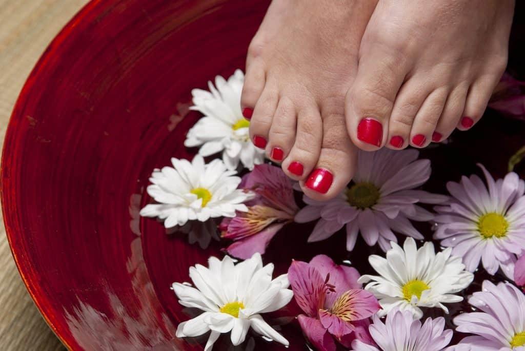 Imagem de pés femininos em uma bacia com água e flores.