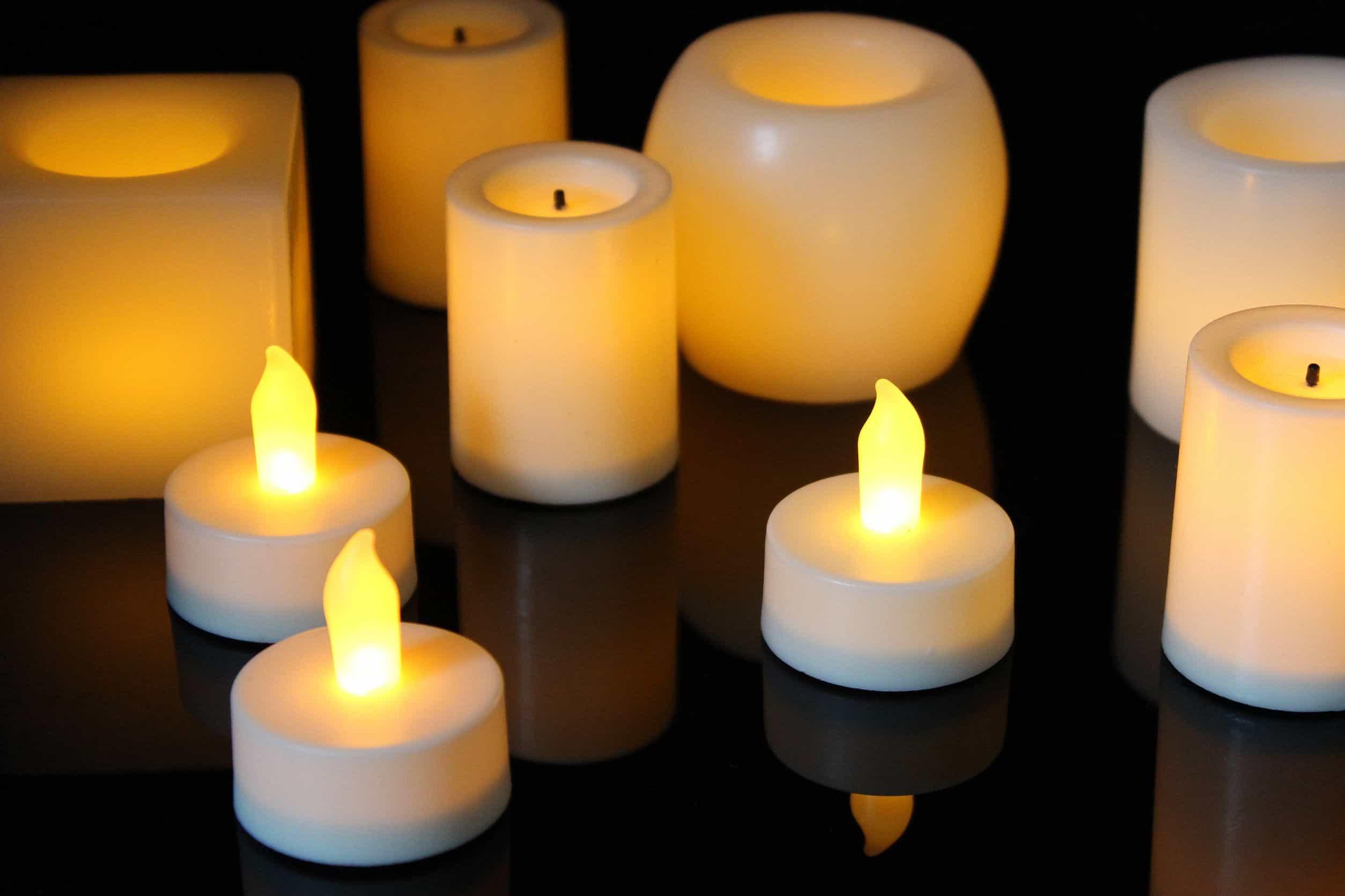 Imagem com velas de diferentes formatos em uma superfície preta.