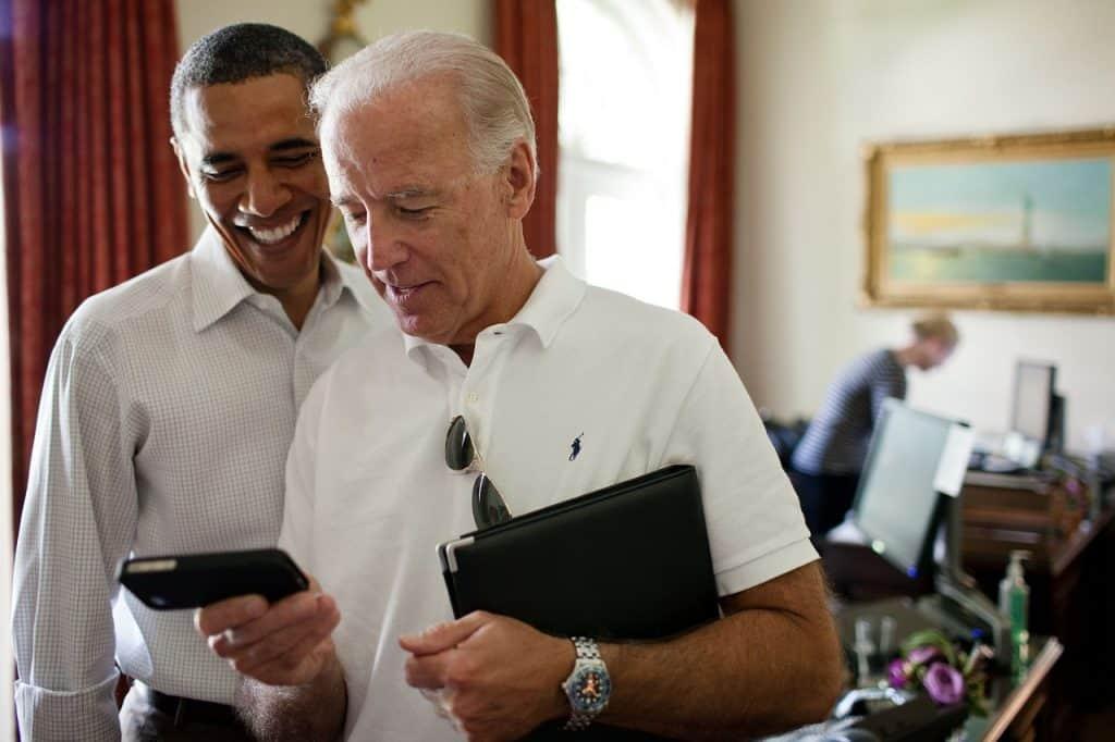 Barack Obama está ao lado de um homem que segura um Iphone com capa.