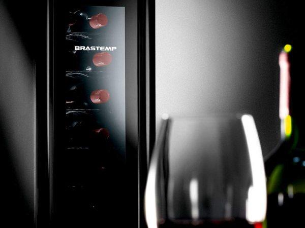 Imagem de adega climatizada Brastemp com destaque para garrafa e taça de vinho