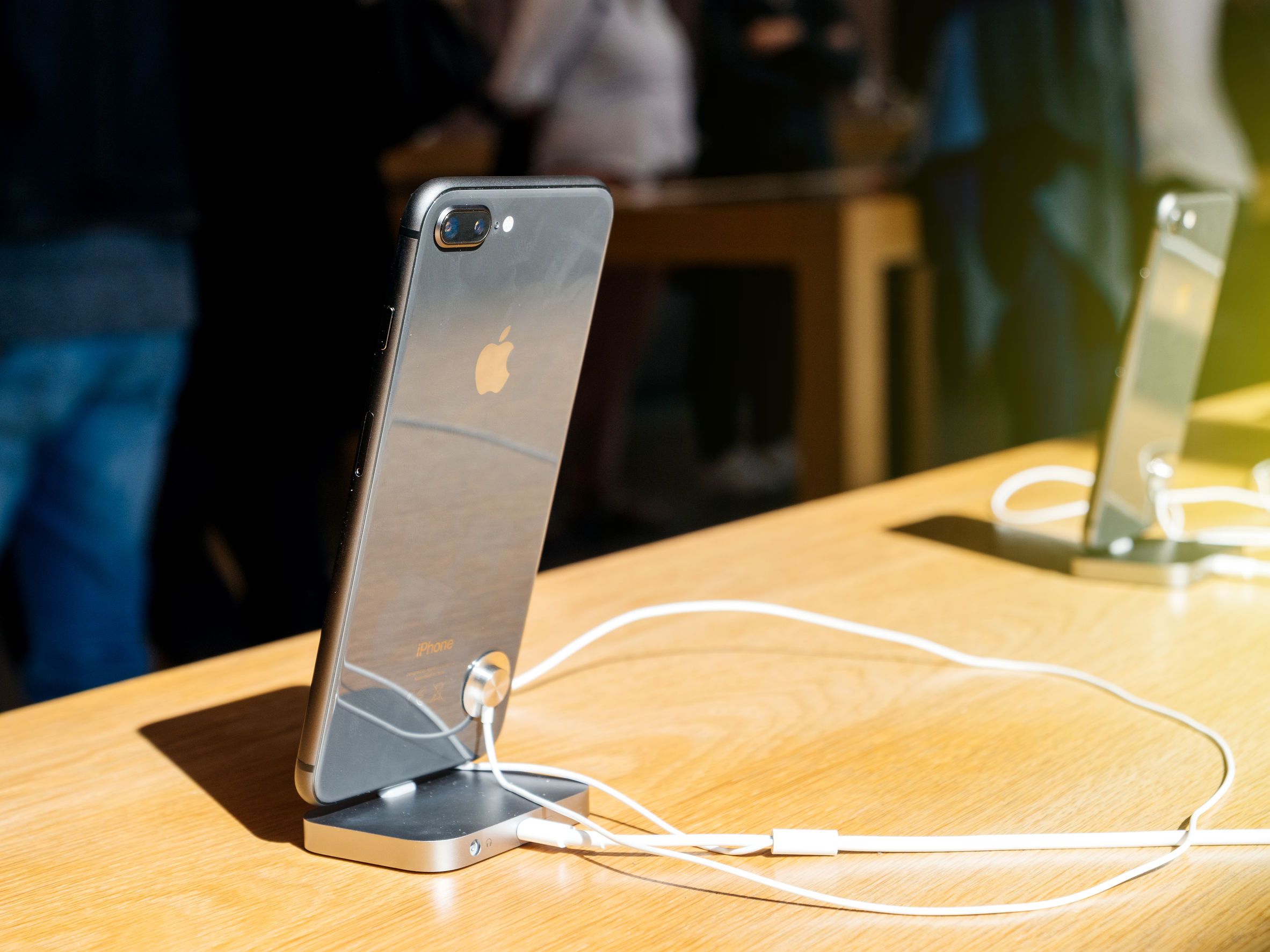 Foto de dois celulares, um em primeiro plano e em um segundo, em cima de uma mesa, conectados a um dock station.