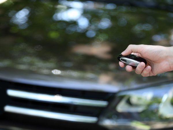 Imagem foca numa mão pressionando o controle de um alarme automotivo. Ao fundo, é possível ver a parte frontal do carro, desfocada.