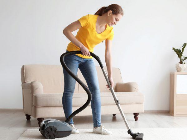 Imagem de uma mulher utilizando um aspirador de pó.
