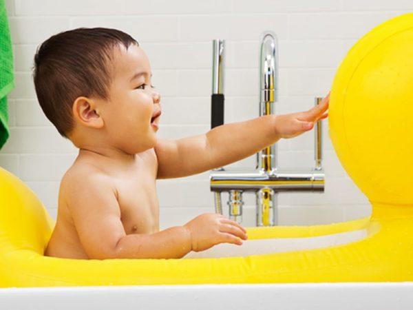 Na foto um bebê dentro de uma banheira em formato de pato.