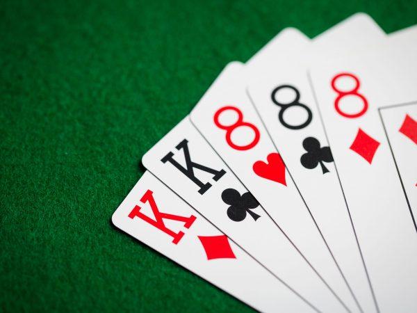 """Mostra uma """"mão"""" de quatro cartas, sendo dois reis e dois oitos, sobre uma superfície de veludo."""