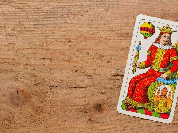 Imagem mostra uma carta de baralho o rei - sobre uma superfície de madeira.