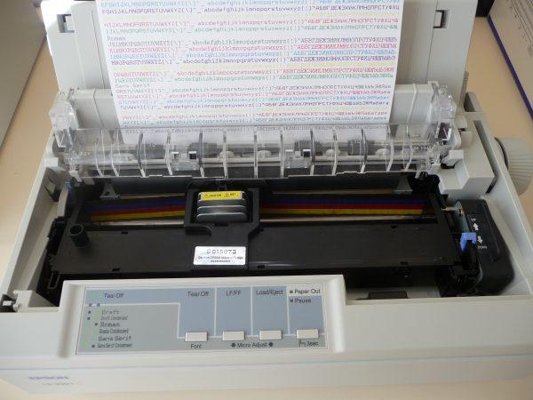 A imagem mostra uma impressora matricial fazendo uma impressão colorida