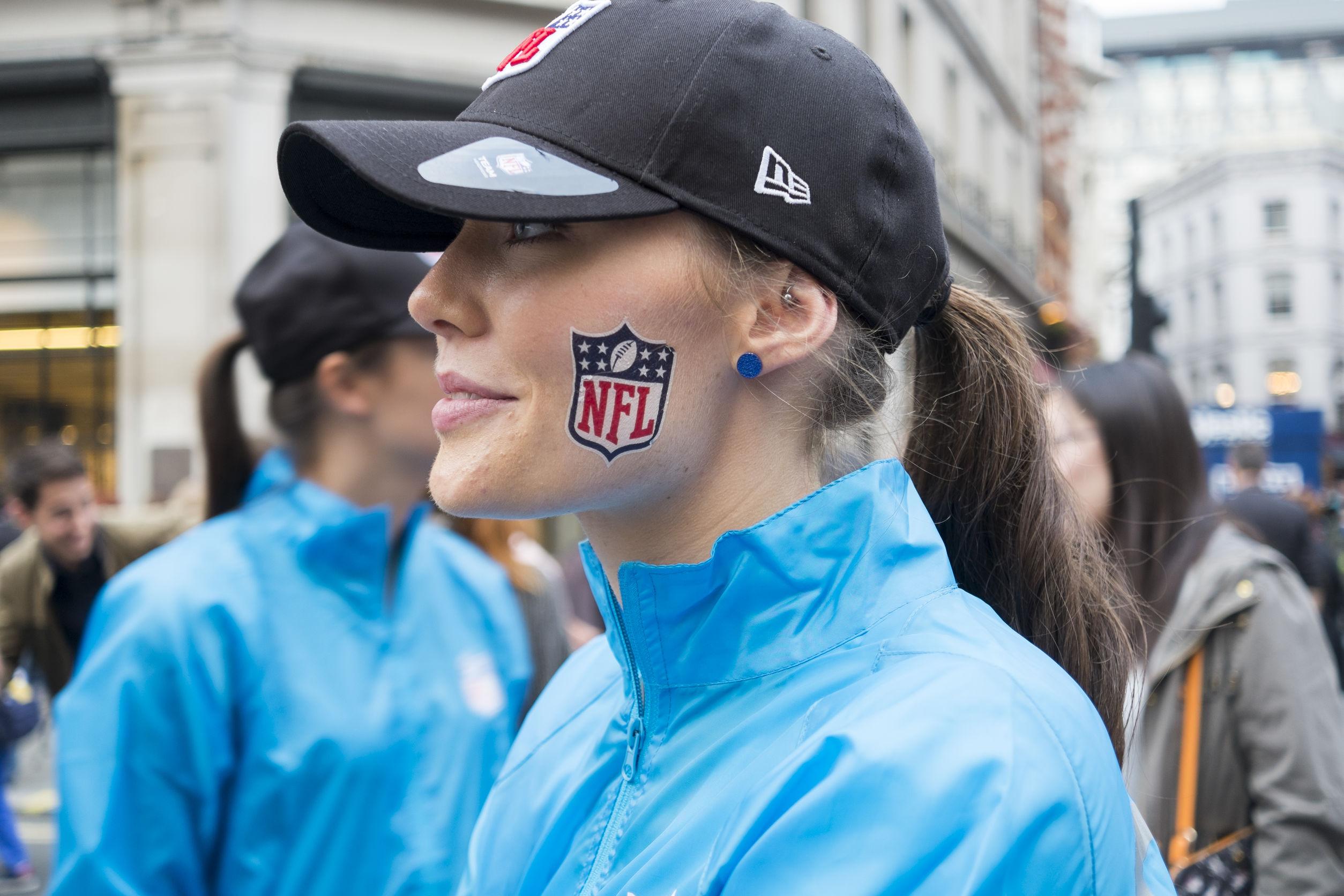 Imagem mostra uma mulher usando um boné NFL e com uma pintura do logotipo da NFL no rosto.