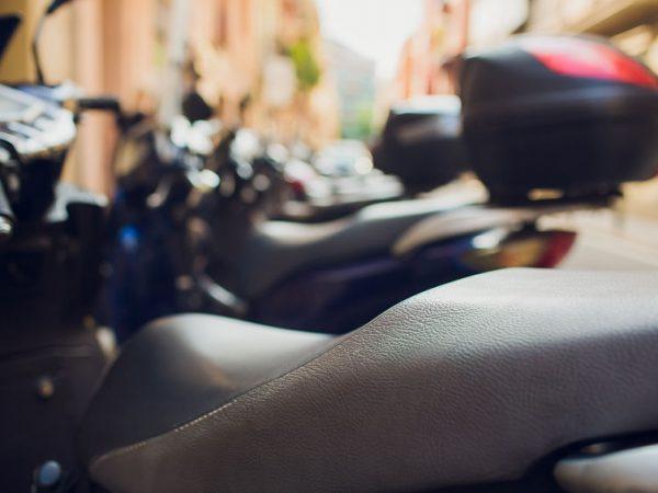 Imagem mostra uma motocicleta com capa de banco em close.