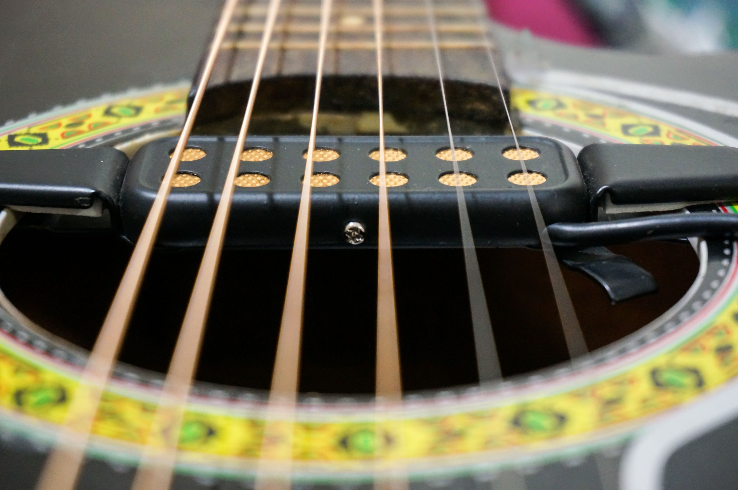 Imagem mostra o close de um captador, em foco seletivo, instalado logo abaixo das cordas de um violão acústico.