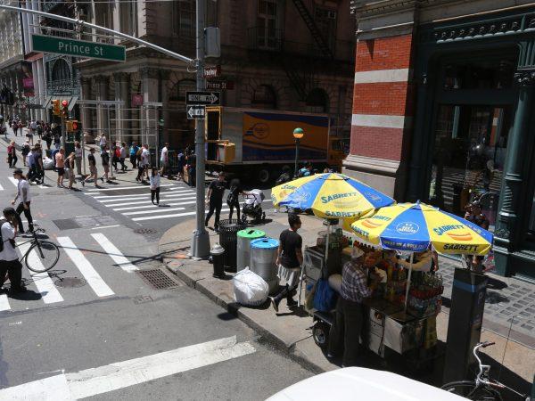 Um carrinho de cachorro quente rodeado de pessoas em uma calçada de Nova Iorque.