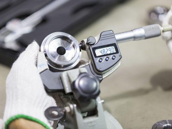 Imagem mostra um manômetro digital sendo manuseado por duas mãos com luvas e medindo uma peça automotiva.