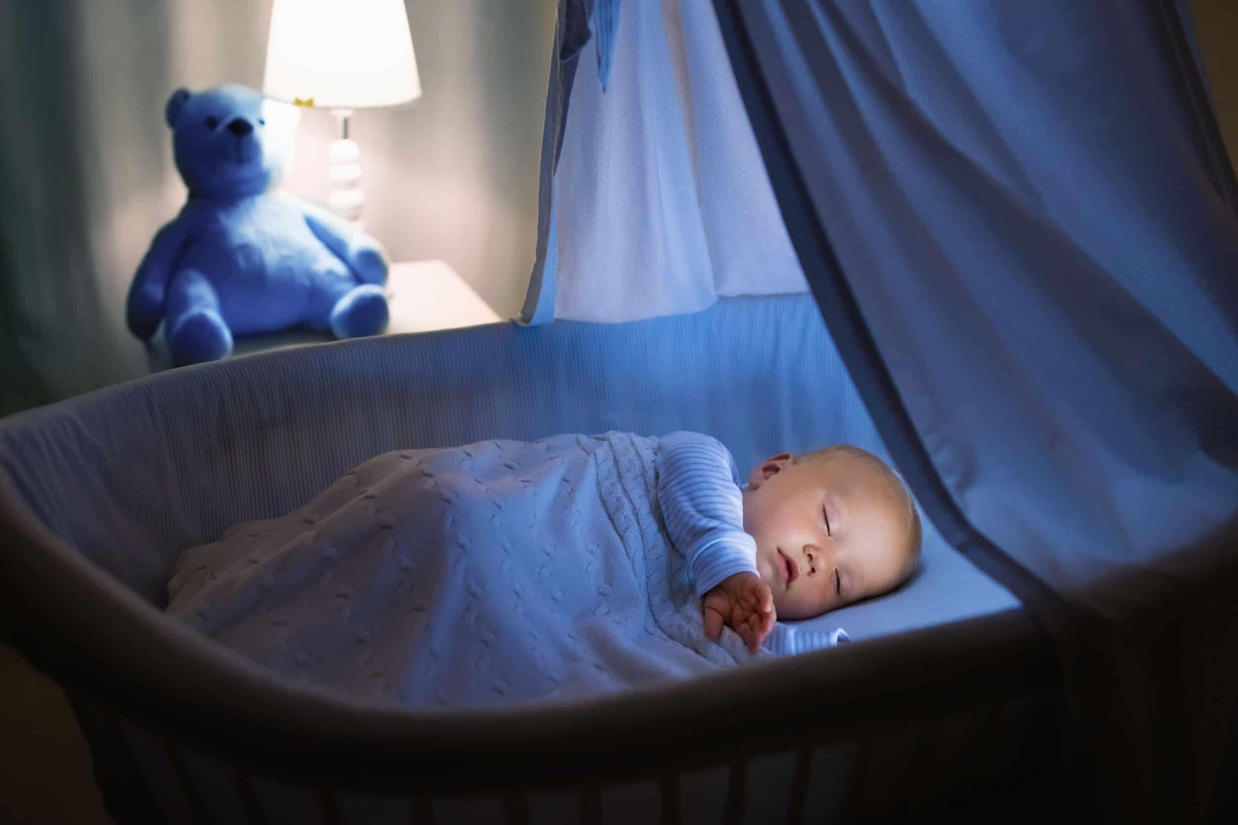 Na foto um bebê dormindo em um berço.