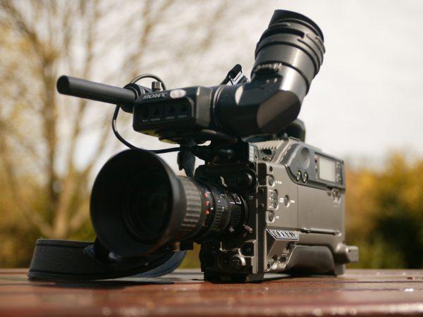 Na foto uma filmadora da Sony em cima de uma mesa de madeira.