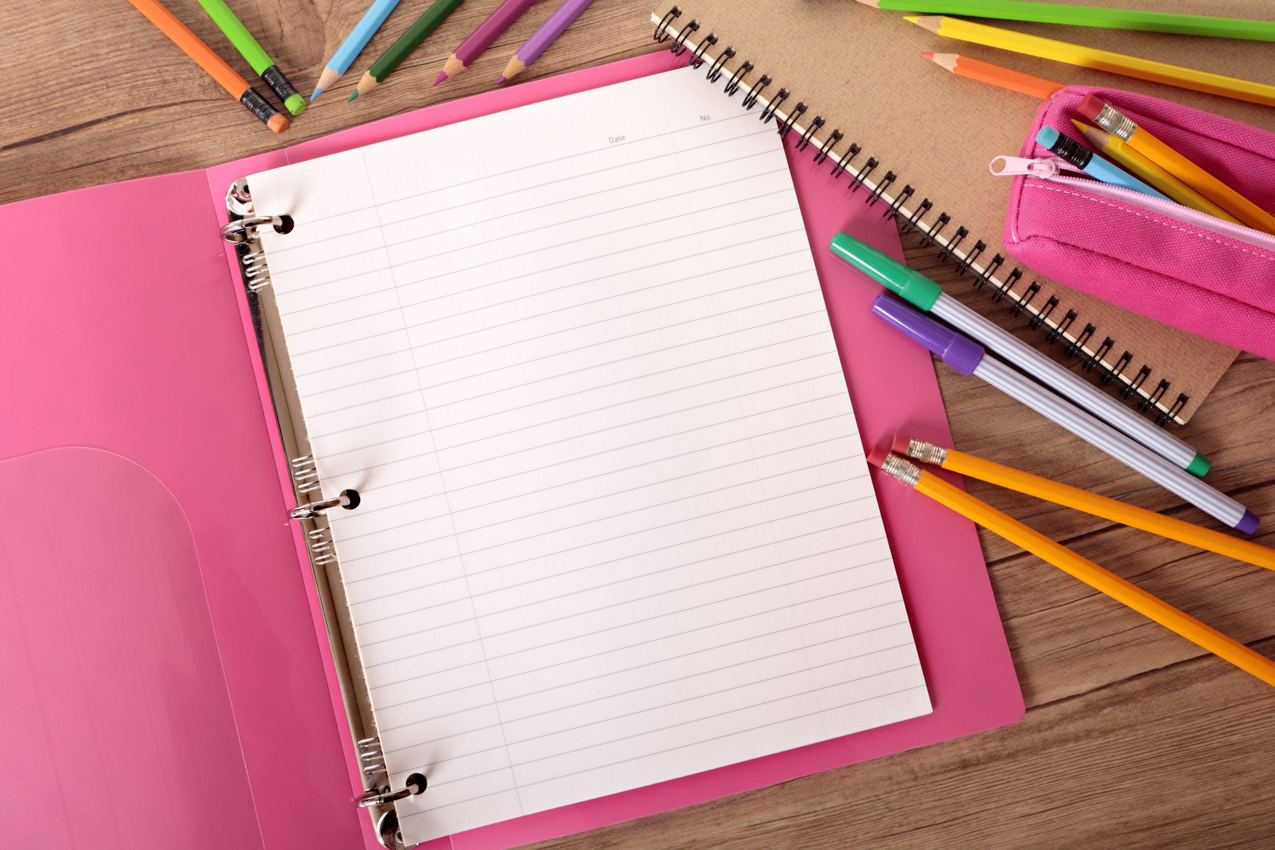 Imagem de folhas dentre de um fichário e em volta várias canetas e lápis.