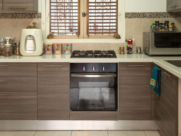 Imagem de um fogão 4 bocas embutido em uma cozinha sob medida organizada.