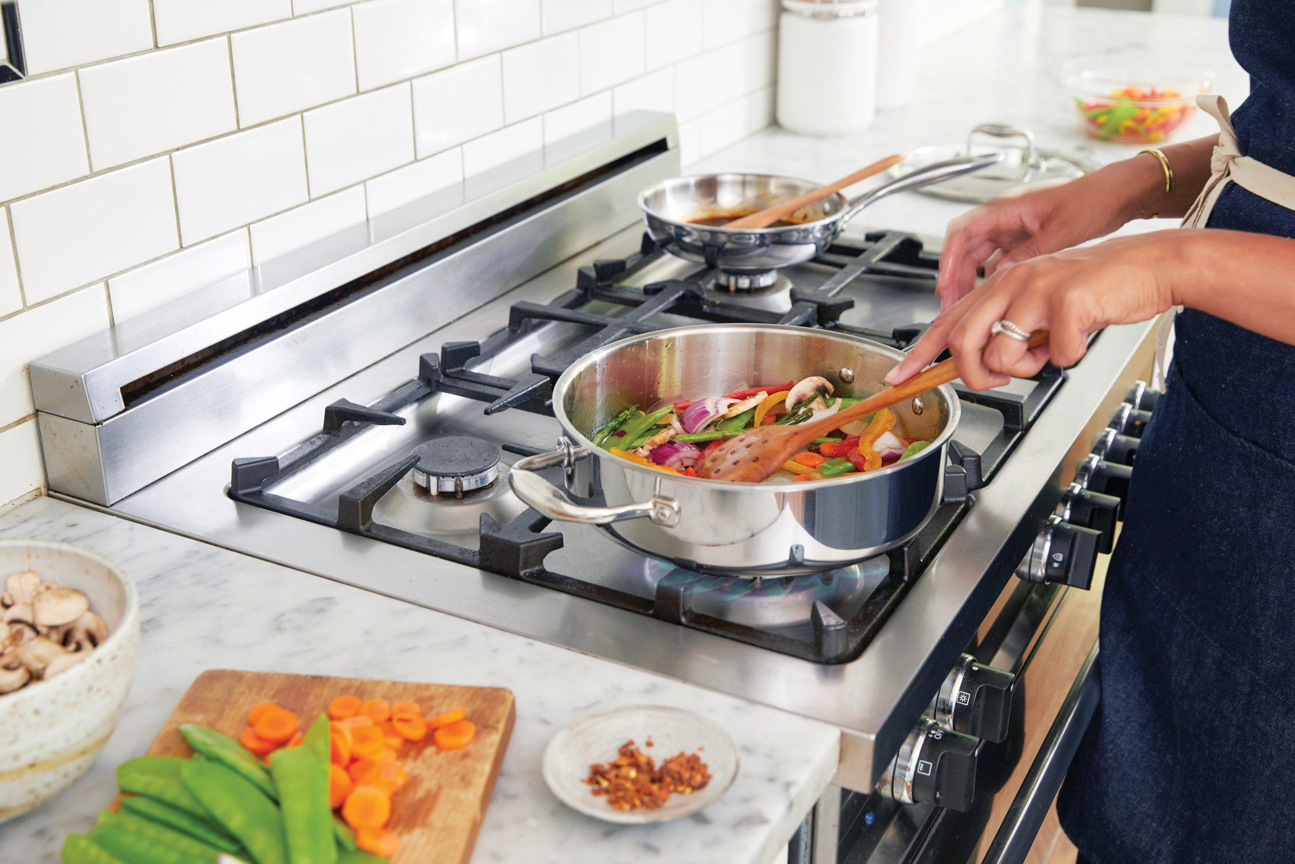 Imagem de uma pessoa cozinhando em um fogão 5 bocas.