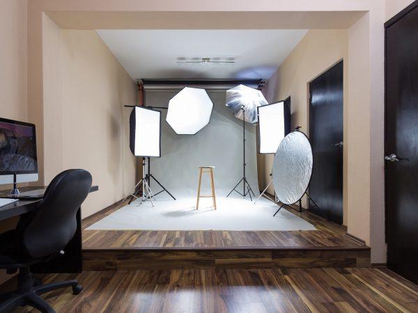 Na foto um estúdio fotográfico com um banco no meio.