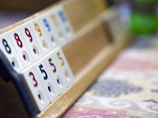 Imagem mostra peças de um jogo de Rummikub, posicionadas na ponta do suporte e retratadas no foco seletivo.