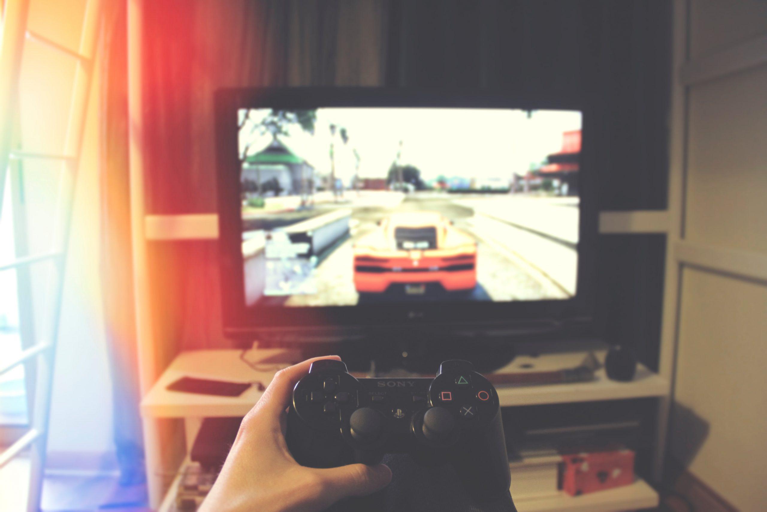 Imagem mostra uma mão segurando um controle de Playstation em frente à uma TV, cuja tela transmite um jogo de carro.