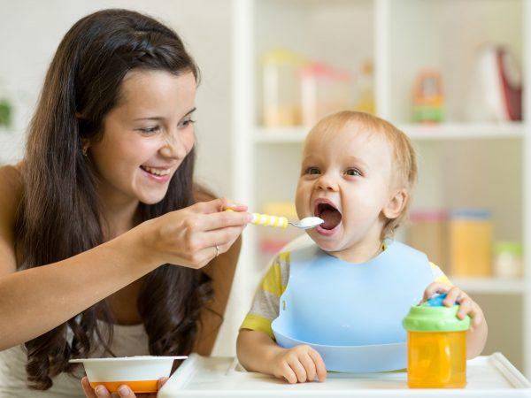 Na foto uma mulher dando comida para um bebê.